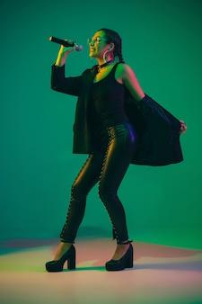 Kaukasisches weibliches gitarristenporträt lokalisiert auf grünem studiohintergrund im neonlicht