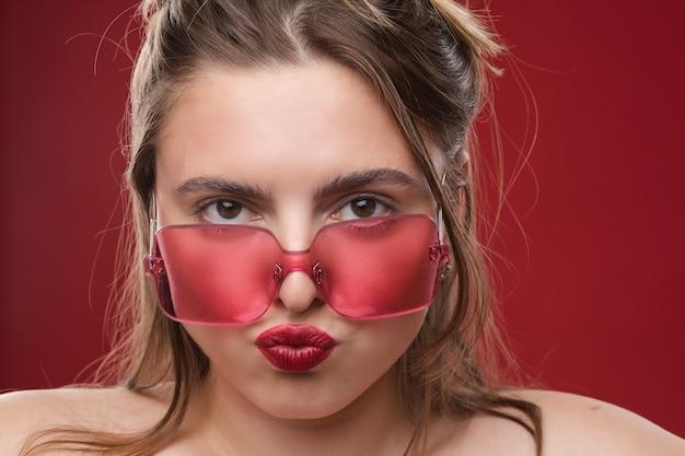 Kaukasisches weibliches model mit langen blonden haaren und großer roter sonnenbrille posiert für die kamera und freut sich