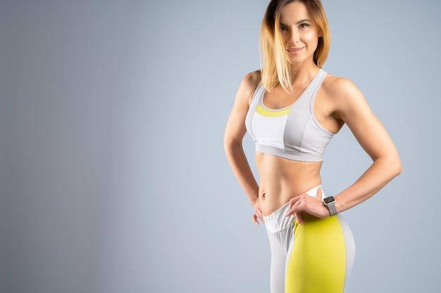 Kaukasisches weibliches modell des jungen sportlichen sitzes auf grauem hintergrund