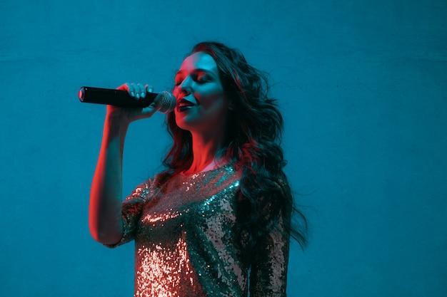 Kaukasisches weibliches sängerporträt lokalisiert auf blauem studiohintergrund im neonlicht. schönes weibliches modell im hellen kleid mit mikrofon. konzept menschlicher emotionen, gesichtsausdruck, werbung, musik, kunst.