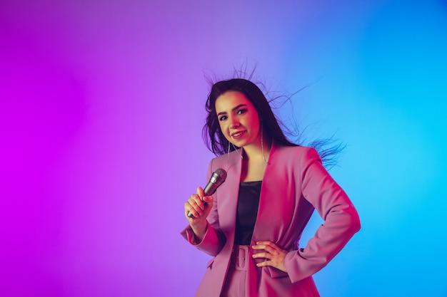 Kaukasisches weibliches sängerporträt lokalisiert auf steigungsstudiohintergrund im neonlicht
