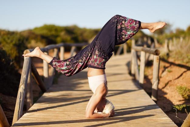Kaukasisches weibliches übendes yoga auf holzbrücke.
