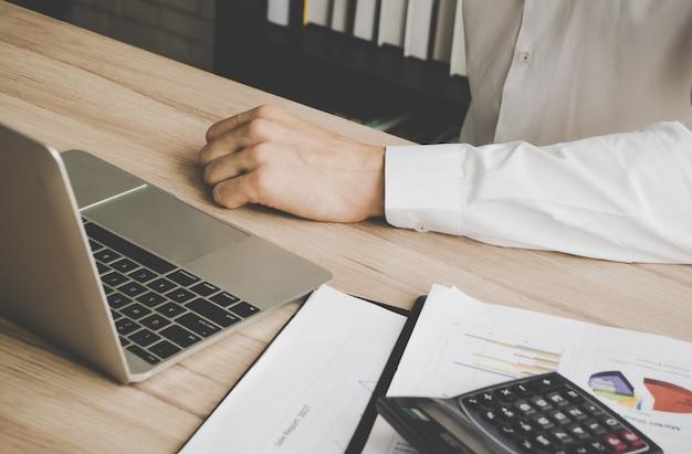 Kausale arbeitskrafthand, die unter verwendung des computerlaptops schreibt