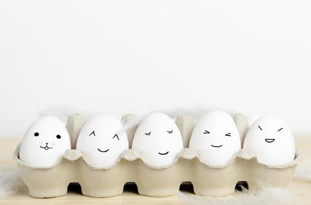 Kawaii gesicht eier in einem karton mit federn auf einem weißen hintergrund.