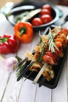 Kebab gekocht auf metallspießen mit gemüse auf weißem tisch serviert