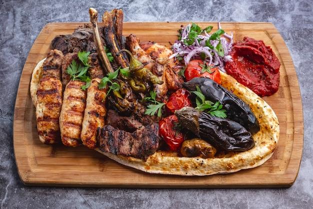 Kebab-platte mit gegrilltem gemüse mit lamm- und hühnchen-lula und tikka-kebabs mit rotem zwiebelsalat