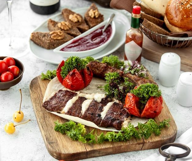 Kebab-platte mit lamm-kebab und gegrilltem tomaten-kebab
