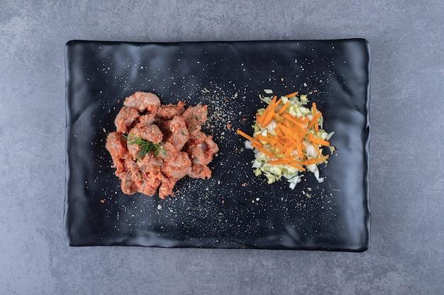 Kebab-stücke und salat auf schwarzem teller.