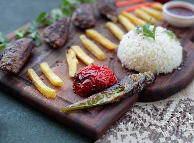 Kebabbrett mit französischen feuern, gegrillten nahrungsmitteln und reis.