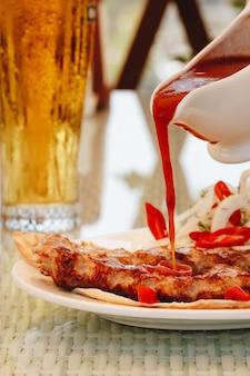 Kebabfleisch mit ketchup auf einem weißen teller gießen sauce im restaurant