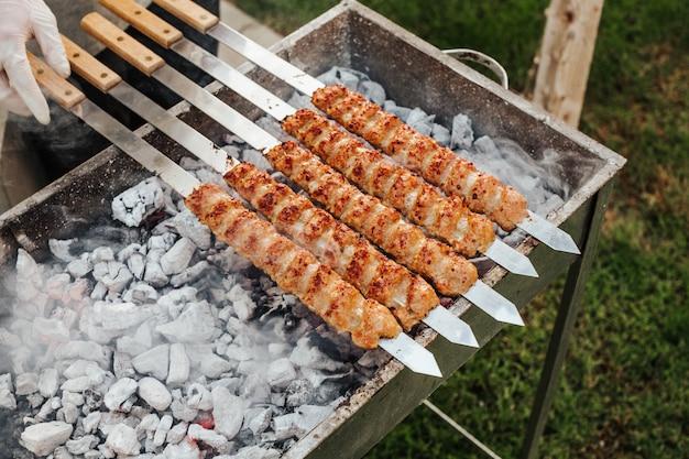 Kebabfleisch mit spießen auf dem grill kochen.
