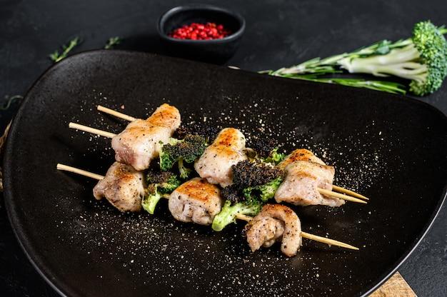 Kebabs - gegrillte fleischspieße, schaschlik mit gemüse. schwarzer hintergrund. ansicht von oben
