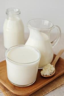 Kefirmilch in glasbehältern und biologische probiotische milchkefirkörner, tibetische pilze