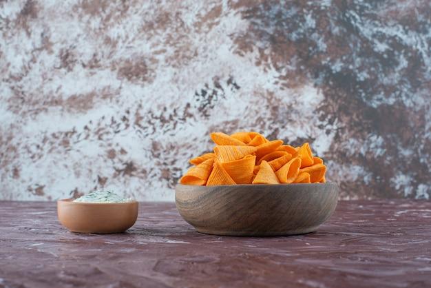 Kegelchips in einer schüssel mit joghurt in einer schüssel auf der marmoroberfläche