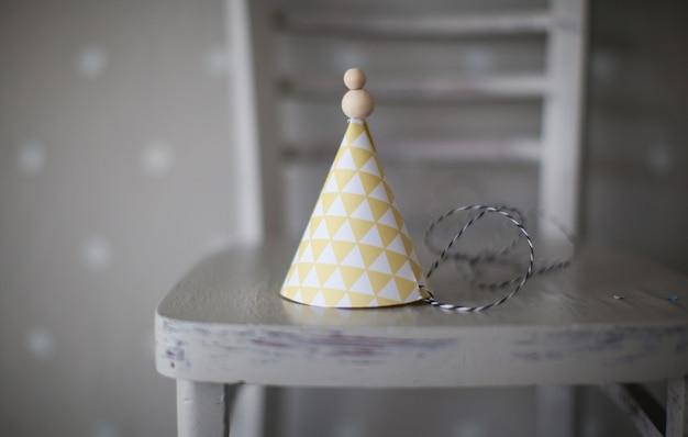 Kegelclownhut mit den gelben und weißen mustern auf einem stuhl