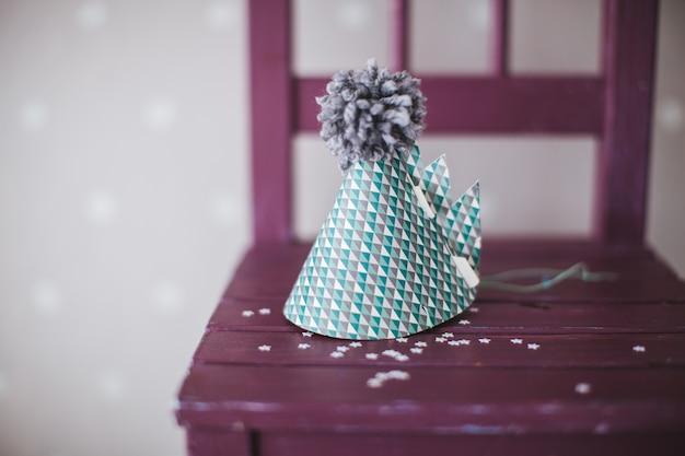Kegelclownhut mit grauem bumbon auf einem stuhl