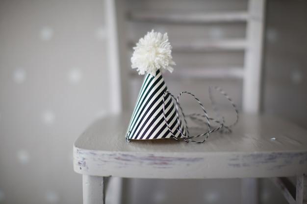 Kegelclownhut mit schwarzweiss-streifen und weißem bumbon auf einem stuhl