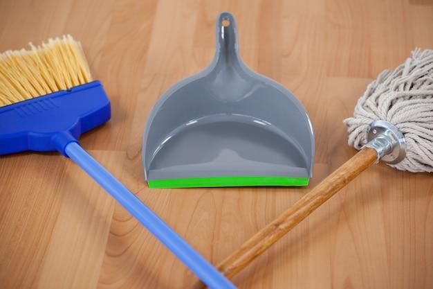 Kehrschaufel, ausgedehnter besen und mopp auf bretterboden