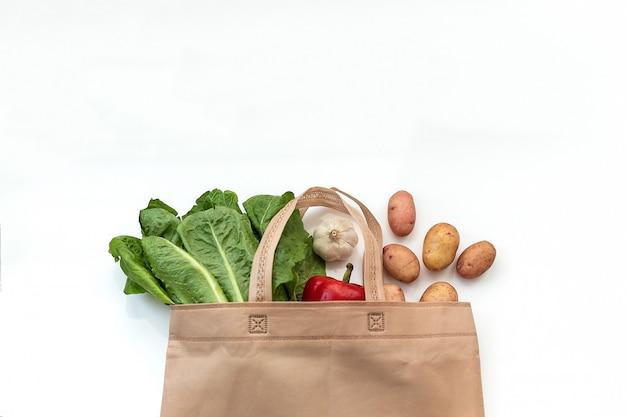 Kein abfall, weniger plastik verwenden frisches gemüse aus bio-baumwolle in stoffbeuteln auf weißer stoffhülle aus holztisch von marktfreiem plastikeinkauf