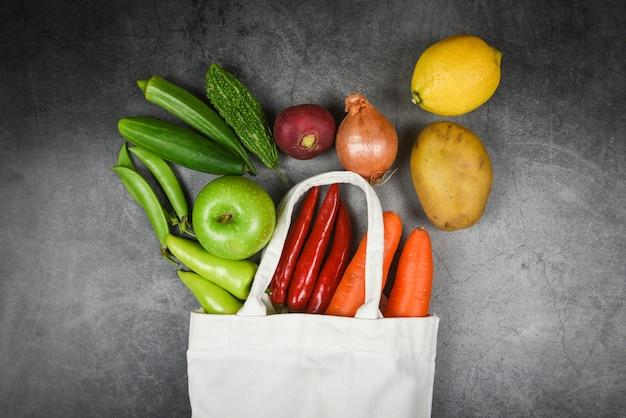Kein abfallverbrauch weniger plastikkonzept - frischgemüse und frucht organisch in den eco baumwollgewebetaschen auf tischdecken-segeltuch-stofftasche vom freien plastikeinkaufen des marktes