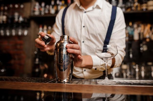 Kein barkeeper im weißen hemd macht einen cocktail