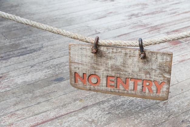 Kein eintrittsholzschild mit altem seil auf altem hölzernem hintergrund