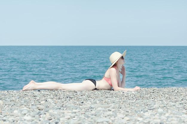 Kein gebräuntes mädchen liegt mit hut und sonnenbad am strand.