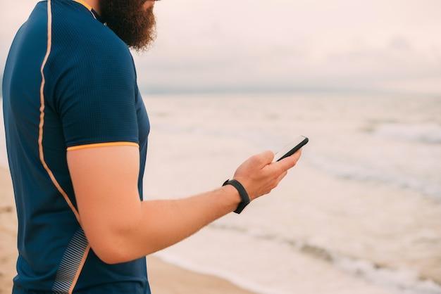 Kein gesichtsfoto eines bärtigen starken mannes, der am strand steht und auf das telefon schaut.