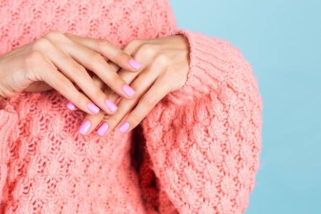 Kein gesichtsfoto von frauenhänden mit hellrosa nagelfarbe maniküre an der wand