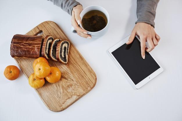 Kein grund zur eile. morgen- und technologiekonzept. junge frau, die in der küche sitzt, tee trinkt und frühstück isst, während feed über digitales tablett scrollt. oberer schuss der hände mit gadget