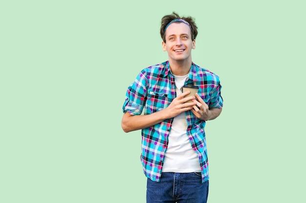 Kein leben ohne kaffee. hübscher junger erwachsener hipster-mann in weißem t-shirt und kariertem hemd, der pappbecher mit morgenkaffee hält und liebe und presse zum herzen zeigt. indoor, isoliert, studioaufnahme