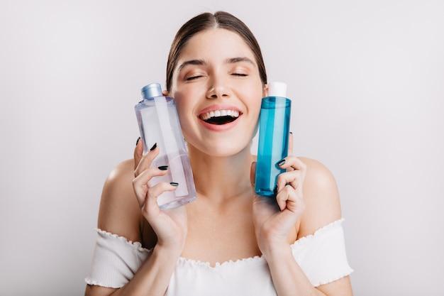 Kein make up. hübsche dame mit perfekter haut hält kosmetisches tonikum um ihr gesicht, um ein gesundes aussehen zu erhalten.