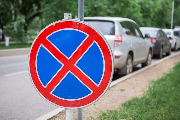 Kein parkverkehrszeichen auf unscharfem autohintergrund. kein parkplatz hier straßenschild