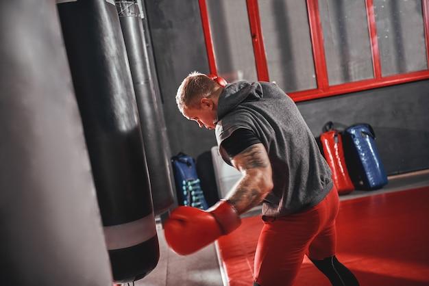 Kein schmerz, kein gewinn, selbstbewusster junger boxer in roten sporthandschuhen, der mit schwerem schlag trainiert