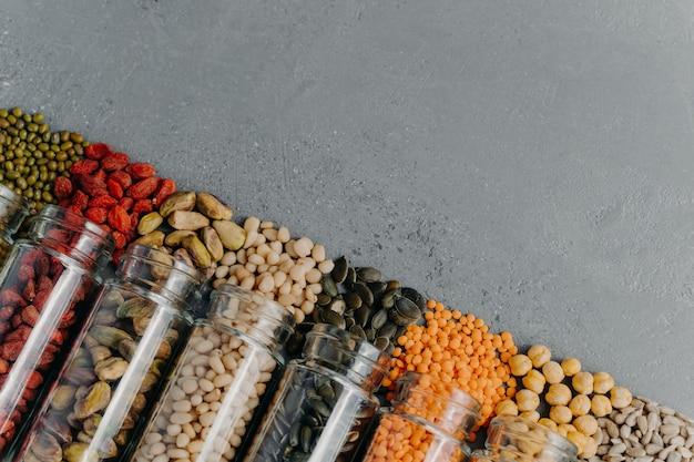 Kein verlust. bio-körner in gläsern. kürbiskerne, kichererbsen, mungobohnen, linsen, goji-beeren, pistazien, aus flaschen verschüttete sonnensamen