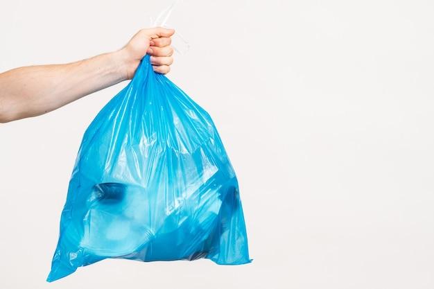 Kein verlust. mannhand hält blaue plastiktüte voll mit müll, auf weißem hintergrund