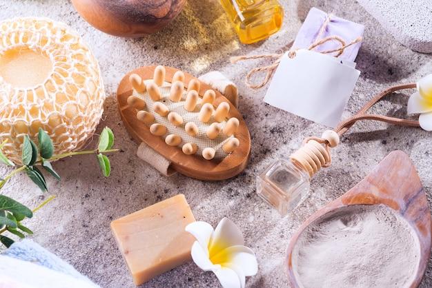 Kein verlust . umweltfreundliches badset. mit pinsel, meersalz, handtuch, aroma in glasflasche, bast auf stein, flach legen
