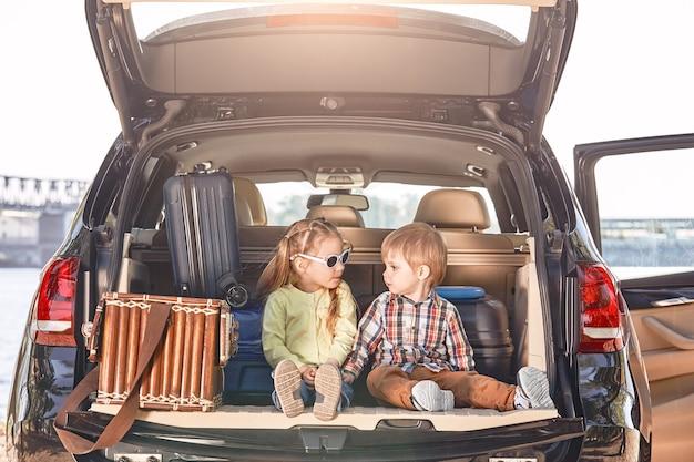 Kein weg ist lang mit guter gesellschaft, kleinen süßen kindern im kofferraum eines
