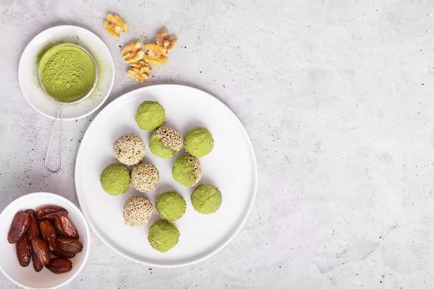 Keine matcha energy bites oder bällchen backen, die mit natürlichen zutaten wie nüssen, matcha-pulver oder datteln zubereitet wurden. draufsicht