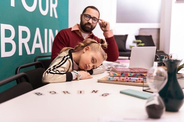 Keine wunschstudie. hübsches blondes mädchen mit armbändern auf ihrer hand, die beim sitzen am tisch verärgert aussehen