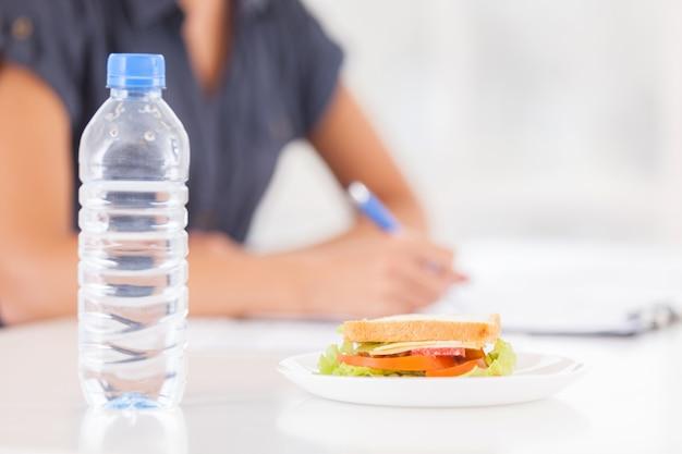 Keine zeit für pause. abgeschnittenes bild einer frau, die etwas in ihren notizblock schreibt, während sandwich und eine flasche wasser im vordergrund liegen