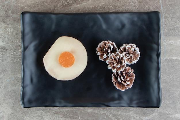 Keks mit marmelade und tannenzapfen auf schwarzem teller