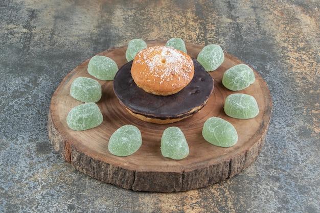 Keks mit schokoladen- und marmeladenbonbons auf holzstück