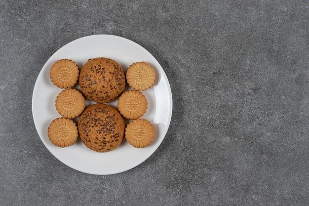 Keks und keks auf dem teller auf der marmoroberfläche