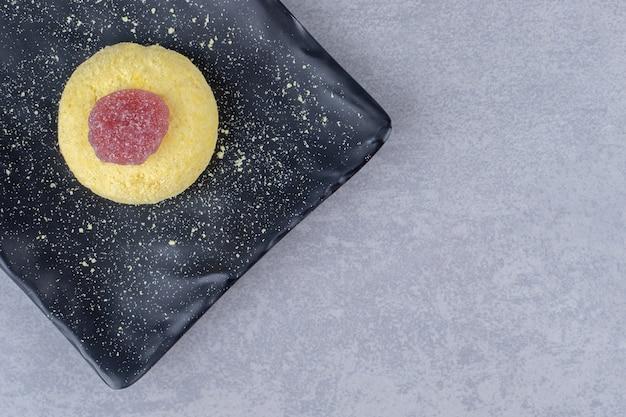 Keks und marmelade auf einer schwarzen platte auf marmor angeordnet