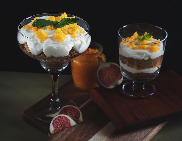 Keksdessert mit sahne und orangenquark im glas