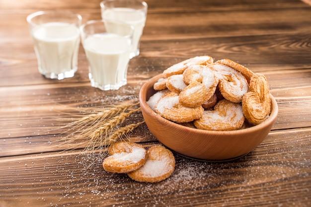 Kekse auf dem teller neben weizenkörnern und tasse mit milch