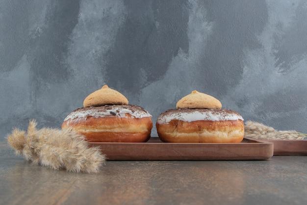 Kekse auf donuts auf holzbrett auf holztisch