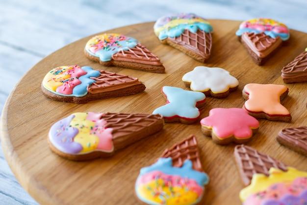 Kekse auf einem holzbrett. bunte glasierte kekse. feiertagsdesserts für kinder. gebäck mit zuckerguss.