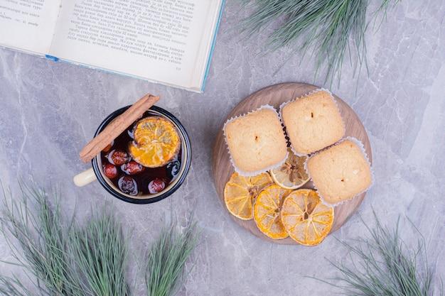 Kekse auf einem holzbrett mit einer tasse tee herum.